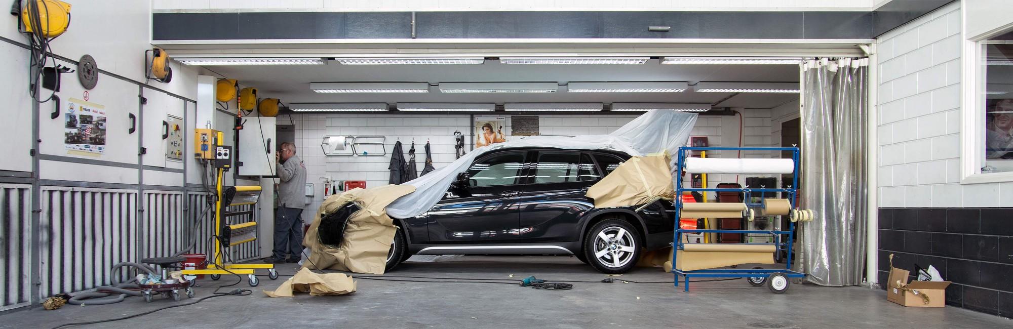 Illustratie: foto van BMW X3 in de werkplaats van X-Pair Autoschade in Naaldwijk. De auto staat er om een reparatie te ondergaan middels spot repair.